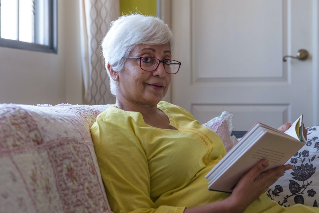 Elderly woman reading a book on the couch